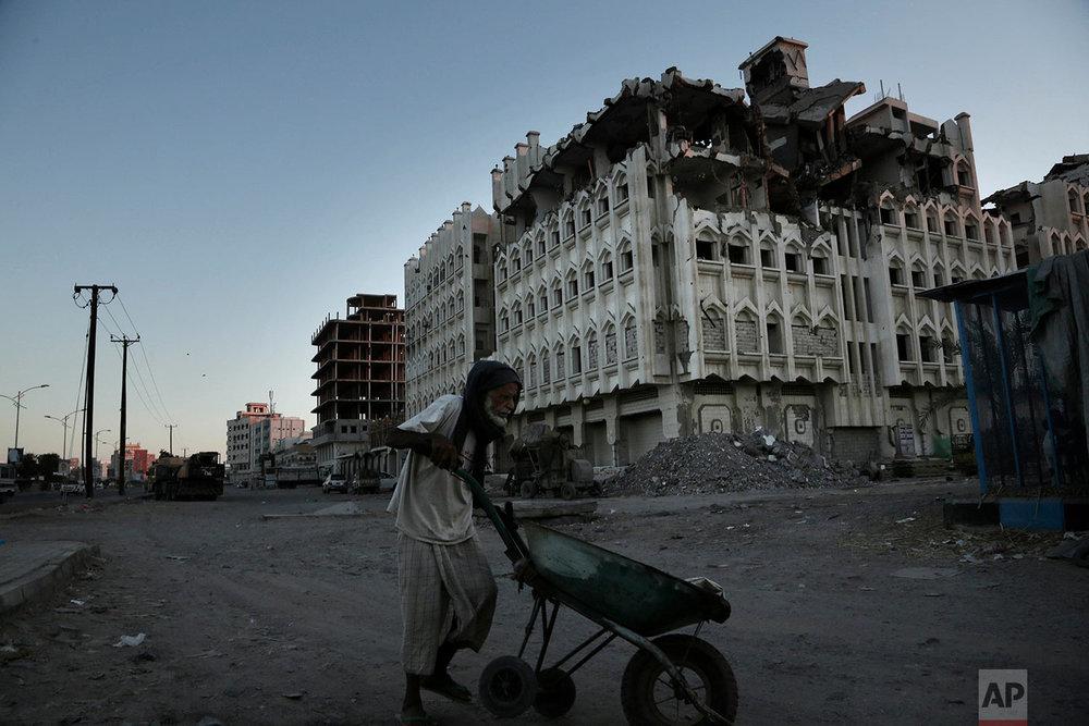 A elderly man walks past a damaged building from the 2015 war in Aden, Yemen. (AP Photo/Nariman El-Mofty)