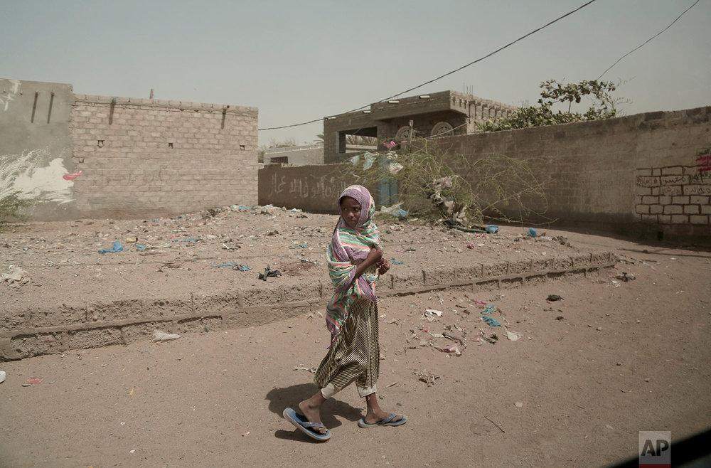 A girl walks alone on a street in al-Khoukha, Yemen.(AP Photo/Nariman El-Mofty)