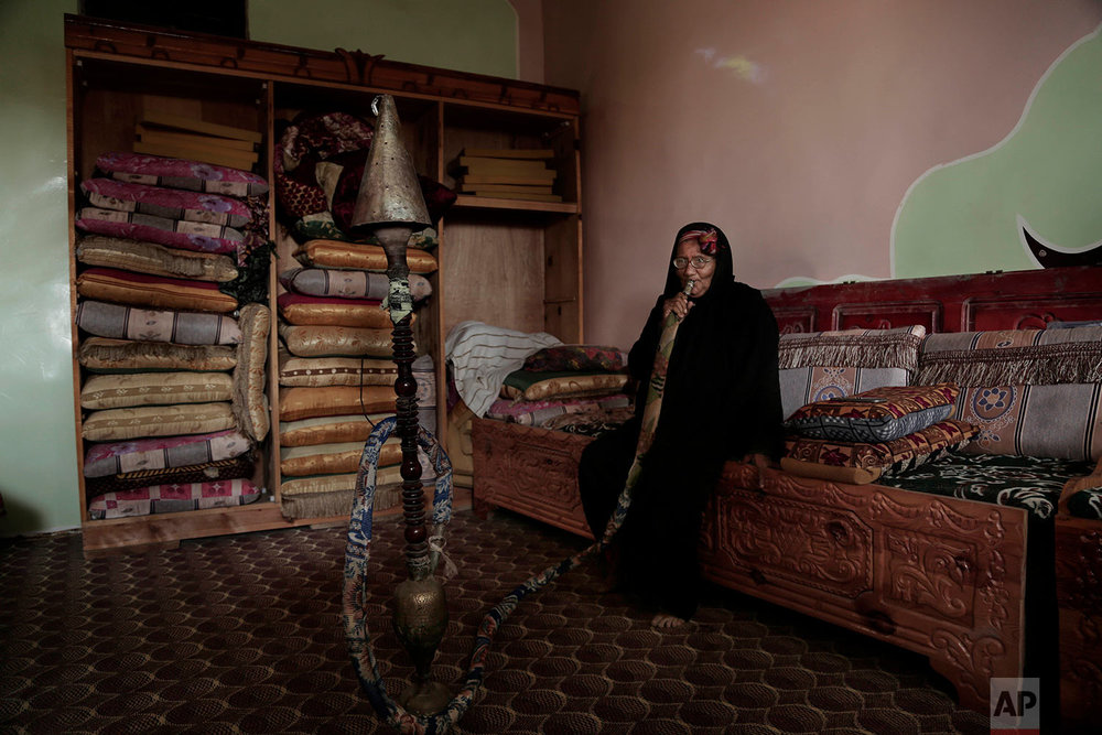 In this Feb. 12, 2018, photo, an elderly woman smokes a water pipe at the home of Ahmed al-Kawkabani, leader of the southern resistance unit in Hodeida, in al-Khoukha, Yemen. (AP Photo/Nariman El-Mofty)