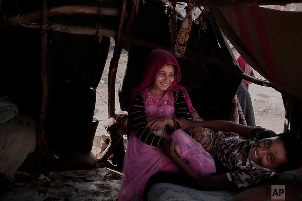 A displaced boy and girl, who are not related and got to know each other recently due to the on-going war, joke in his shelter, in Abyan, Yemen. (AP Photo/Nariman El-Mofty)
