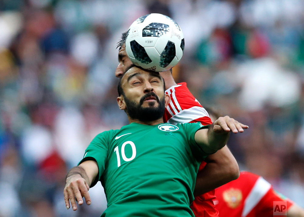 Saudi Arabia's Mohammed Alsahlawi, foreground, jumps for the ball with Russia's Alexander Samedov during the group A match between Russia and Saudi Arabia which opens the 2018 soccer World Cup at the Luzhniki stadium in Moscow, Russia, Thursday, June 14, 2018. (AP Photo/Hassan Ammar)
