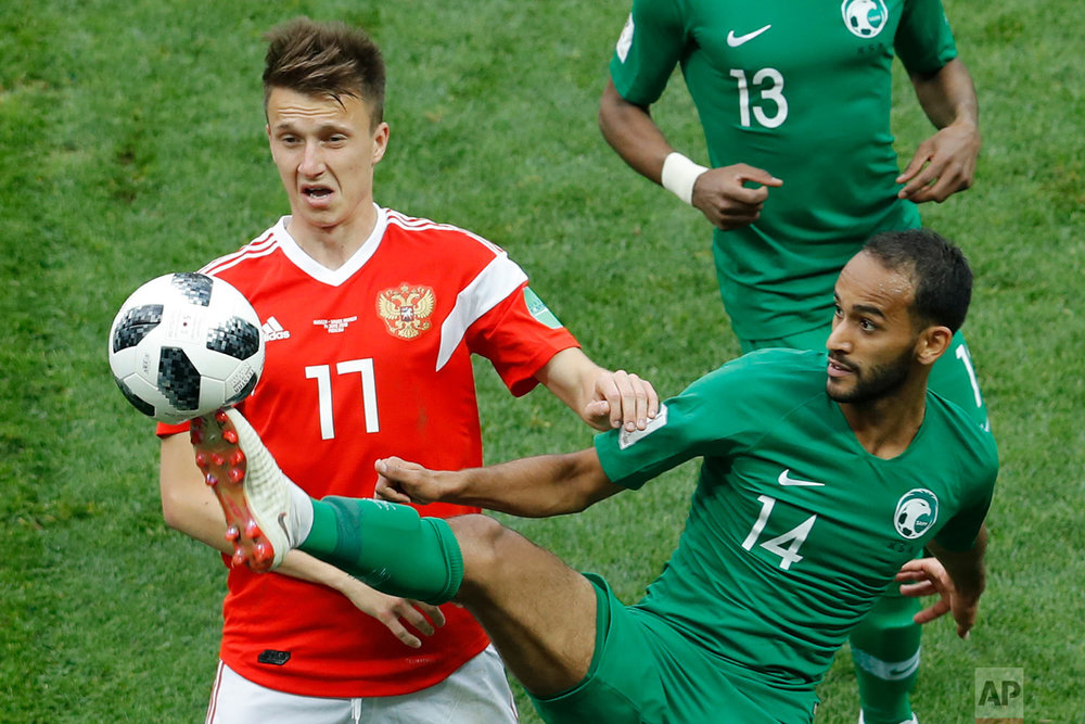 Russia's Roman Zobnin, left, and Saudi Arabia's Abdullah Otayf vie for the ball during the group A match between Russia and Saudi Arabia which opens the 2018 soccer World Cup at the Luzhniki stadium in Moscow, Russia, Thursday, June 14, 2018. (AP Photo/Victor Caivano)