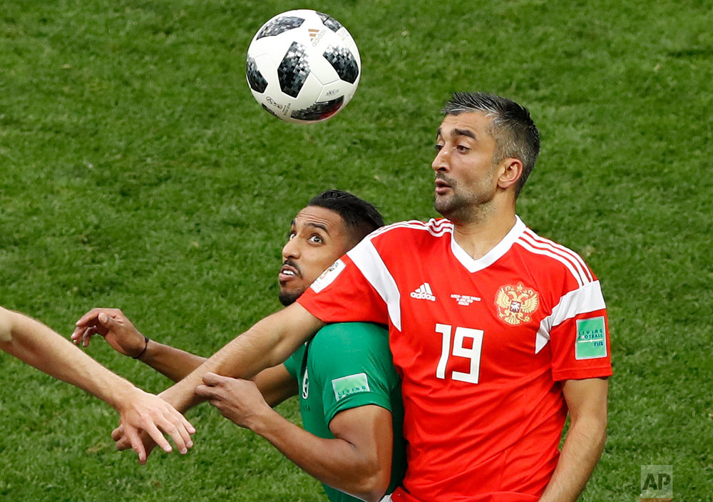 Russia's Alexander Samedov, right, tries to stop Saudi Arabia's Salem Aldawsari, center, during the group A match between Russia and Saudi Arabia which opens the 2018 soccer World Cup at the Luzhniki stadium in Moscow, Russia, Thursday, June 14, 2018. (AP Photo/Darko Bandic)