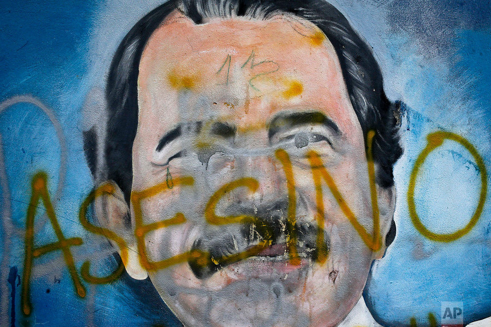 "In this May 26, 2018 photo, the Spanish word for ""Murderer"" covers a mural of Nicaragua's President Daniel Ortega, as part of anti-government protests demanding his resignation in Managua, Nicaragua. (AP Photo/Esteban Felix)"