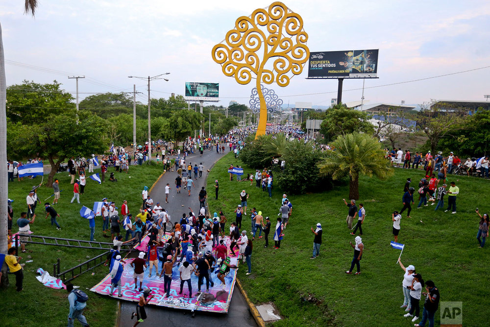 "In this May 20, 2018 photo, a pro-government billboard featuring Nicaragua's President Daniel Ortega and his wife first lady Rosario Murillo is destroyed by protesters, near a ""Tree of Life"" sculpture, a pet project of Murillo, in Managua, Nicaragua. (AP Photo/Esteban Felix)"