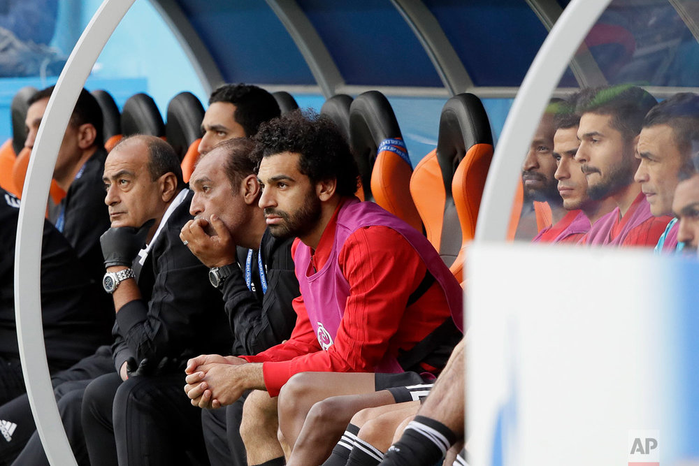Egypt's Mohamed Salah, center, watches his team during the group A match between Egypt and Uruguay at the 2018 soccer World Cup in the Yekaterinburg Arena in Yekaterinburg, Russia, Friday, June 15, 2018. (AP Photo/Mark Baker)