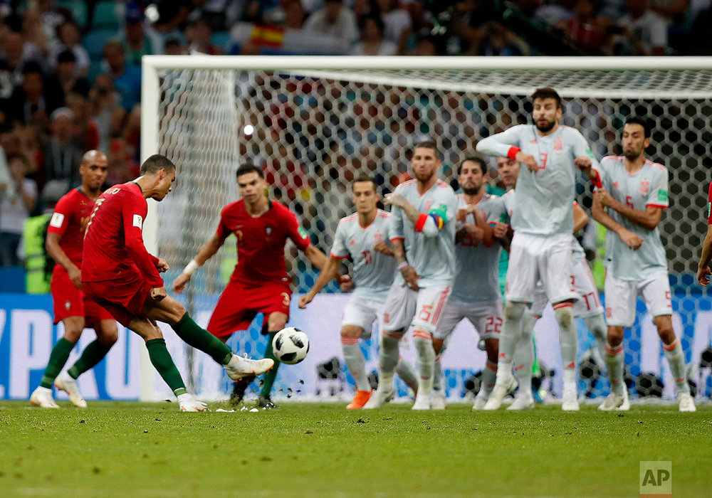 Portugal's Cristiano Ronaldo, left, scores his side's equalizing goal during the group B match between Portugal and Spain at the 2018 soccer World Cup in the Fisht Stadium in Sochi, Russia, Friday, June 15, 2018. (AP Photo/Francisco Seco)