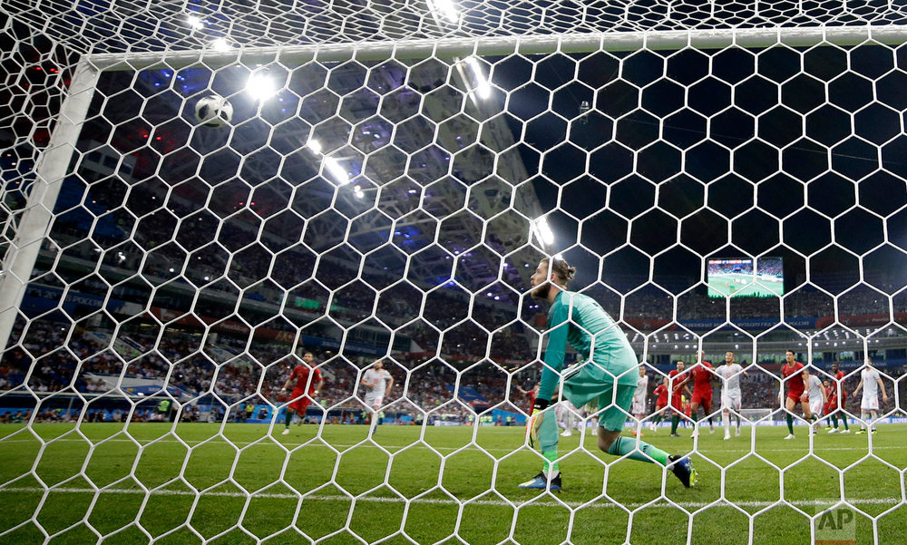 Spain goalkeeper David De Gea looks to the ball when Portugal's Cristiano Ronaldo scores his side's third goal during the group B match between Portugal and Spain at the 2018 soccer World Cup in the Fisht Stadium in Sochi, Russia, Friday, June 15, 2018. (AP Photo/Sergei Grits)