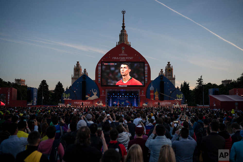 Fans watch on a giant screen as Portugal's Cristiano Ronaldo prepares to kick a penalty during the group B match between Portugal and Spain, at the FIFA Fan Fest in Moscow, Russia, Friday, June 15, 2018. (AP Photo/Felipe Dana)