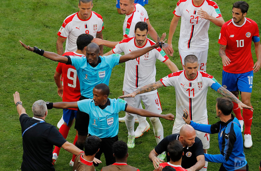 Referee Malang Diedhiou, left, from Senegal and the fourth official Bamlak Tessera Weyesa from Ethiopia go between Costa Rica and Serbia players as they argue during the group E match between Costa Rica and Serbia at the 2018 soccer World Cup in the Samara Arena in Samara, Russia, Sunday, June 17, 2018. (AP Photo/Vadim Ghirda)