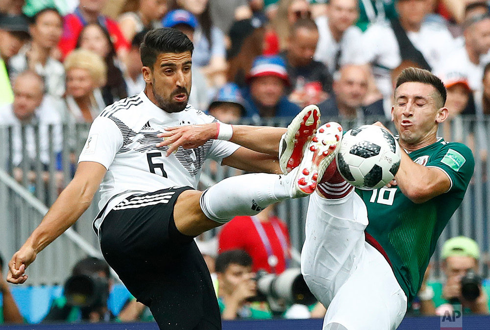 Germany's Sami Khedira, left, and Mexico's Hector Herrera challenge for the ball during the group F match between Germany and Mexico at the 2018 soccer World Cup in the Luzhniki Stadium in Moscow, Russia, Sunday, June 17, 2018. (AP Photo/Matthias Schrader)