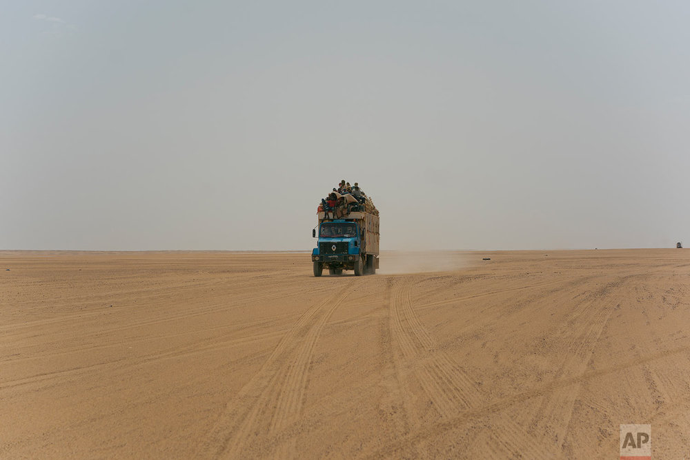 A truck carrying goods and migrants drives through Niger's Tenere desert region of the south central Sahara on Sunday, June 3, 2018. Once a well-worn roadway for overlander tourists, the highway's 4,500 kilometers (2,800 miles) are a favored path for migrants heading north in hopes of a better life - and more recently thousands who are being expelled south from Algeria. (AP Photo/Jerome Delay)