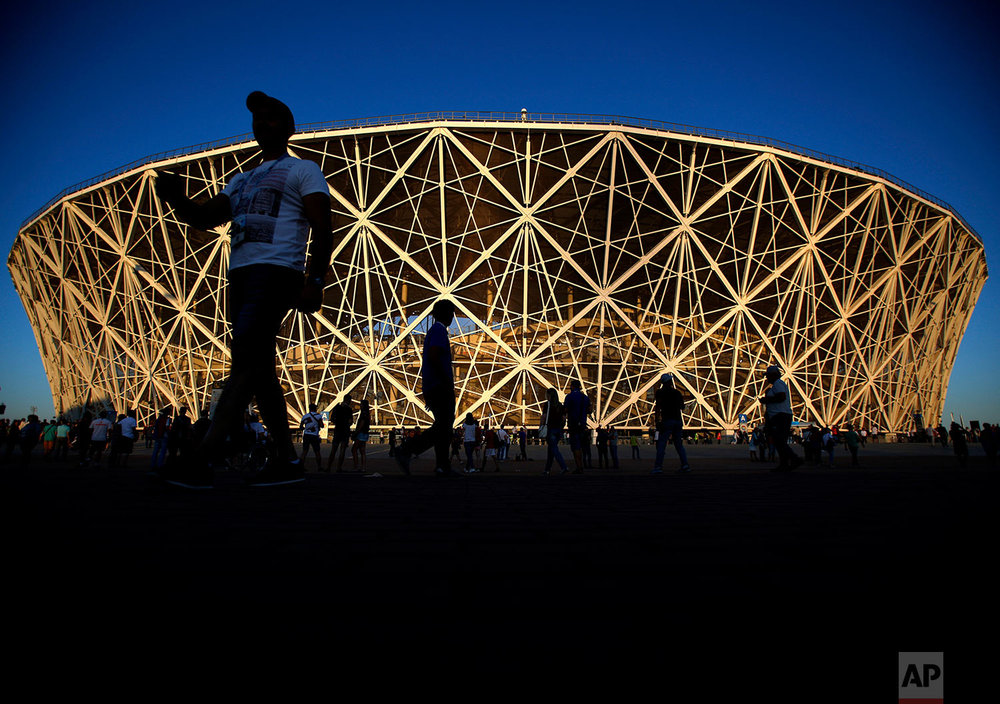 People walk around the stadium before the group G match between Tunisia and England at the 2018 soccer World Cup in the Volgograd Arena in Volgograd, Russia, Monday, June 18, 2018. (AP Photo/Rebecca Blackwell)