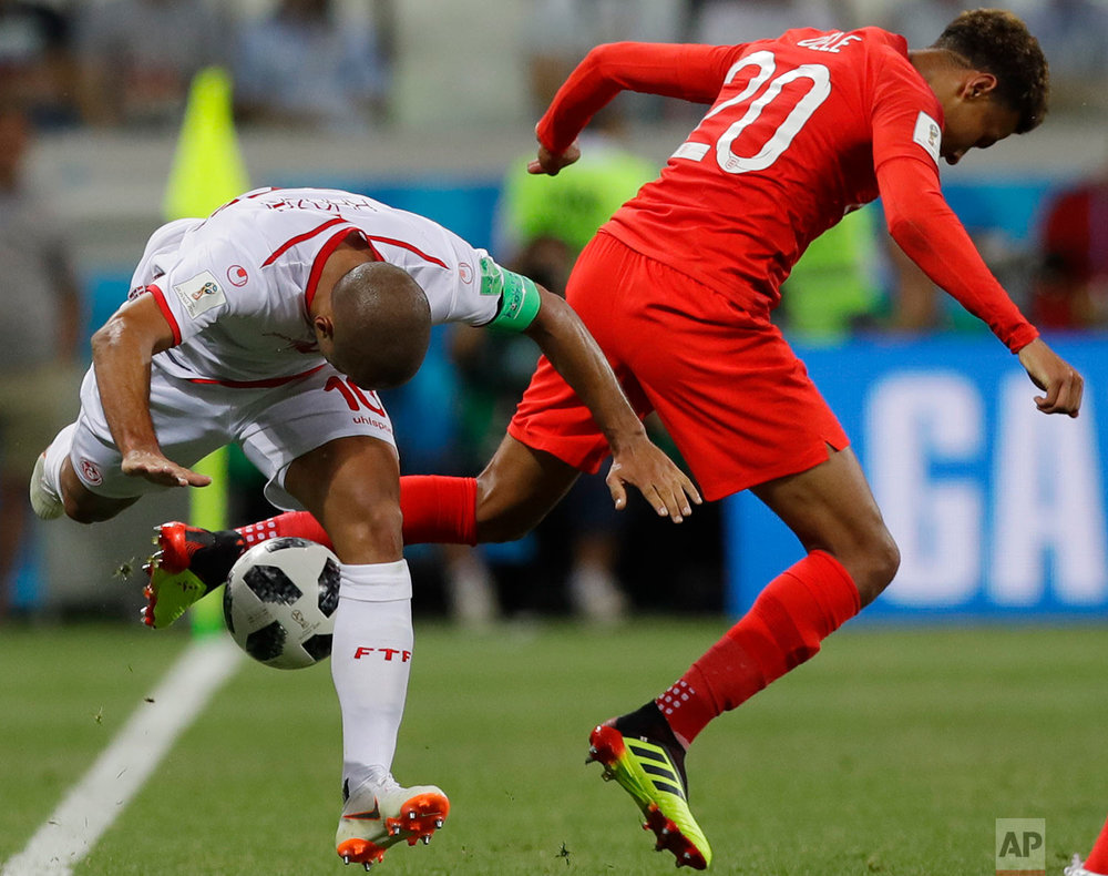 Tunisia's captain Wahbi Khazri, left, and England's Dele Alli compete for the ball during a group G match at the 2018 soccer World Cup in the Volgograd Arena in Volgograd, Russia, Monday, June 18, 2018. (AP Photo/Alastair Grant)
