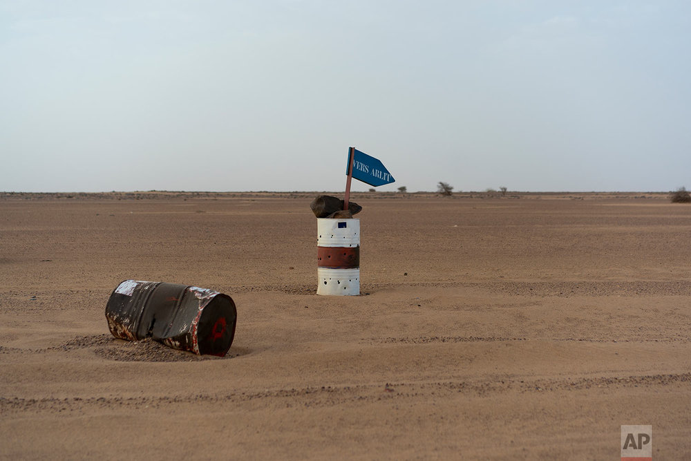 A bullet ridden paired barrel indicates the direction of Arlit in Niger's Tenere desert region of the south central Sahara on June 3, 2018. (AP Photo/Jerome Delay)