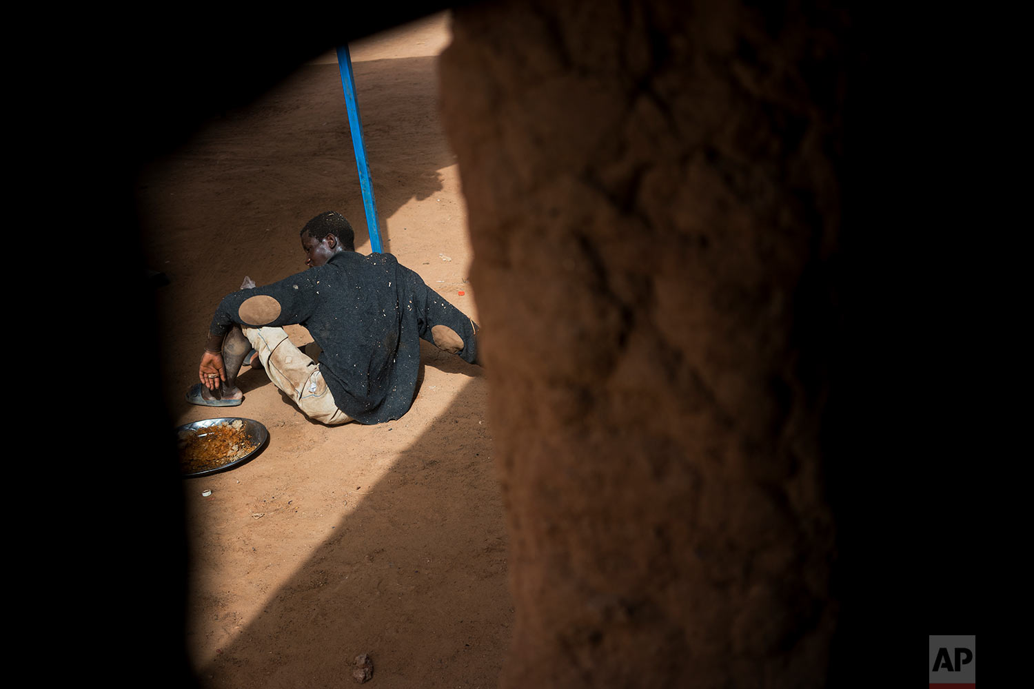A young migrant who has been expelled from Algeria sits in a transit center in Arlit, Niger, on June 1, 2018. (AP Photo/Jerome Delay)
