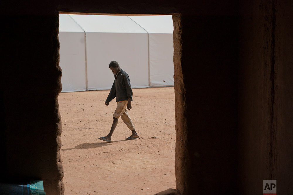A young migrant who has been expelled from Algeria paces in a transit center in Arlit, Niger, on June 1, 2018. (AP Photo/Jerome Delay)