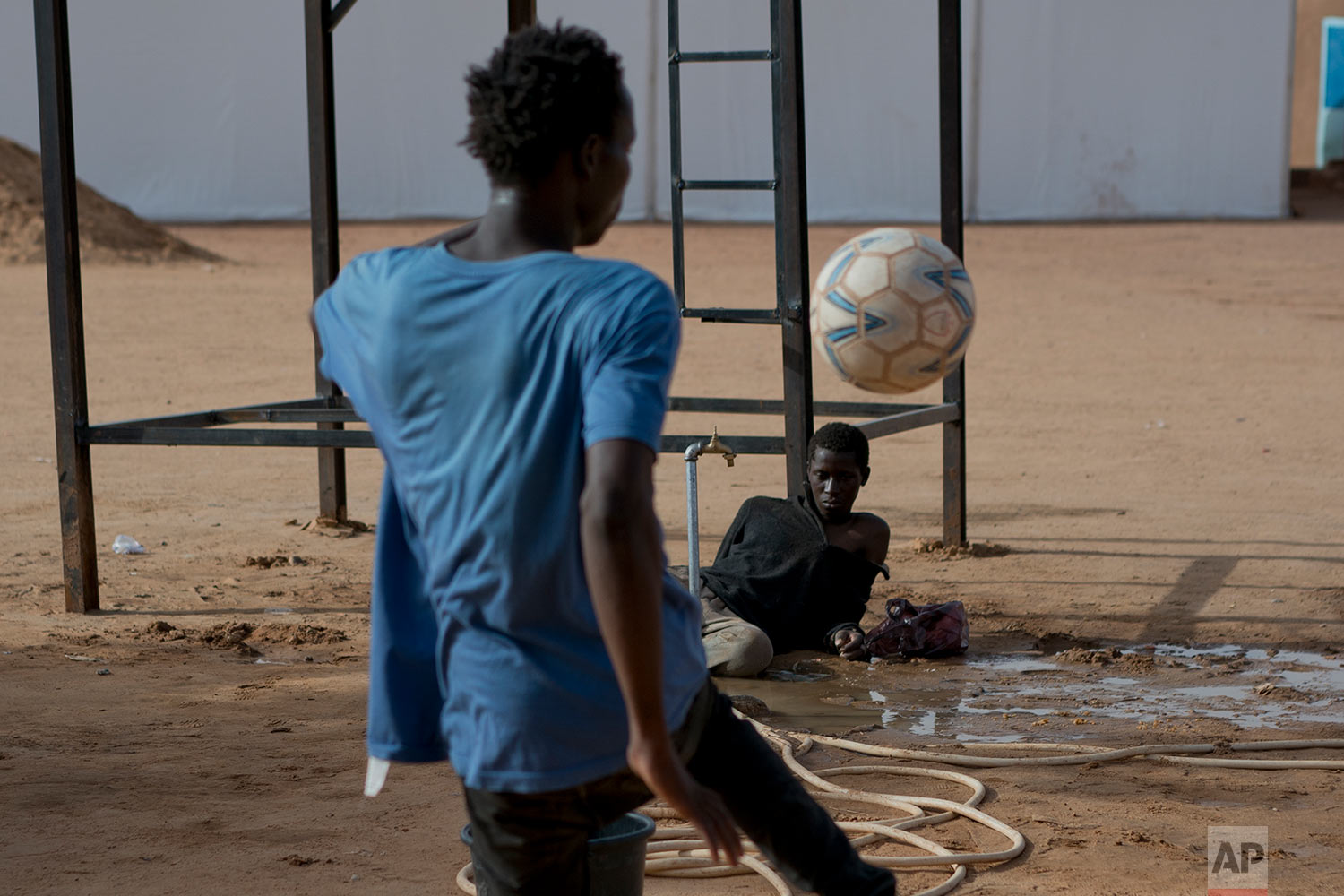A young migrant who has been expelled from Algeria watches others play football in a transit center in Arlit, Niger, on June 1, 2018 (AP Photo/Jerome Delay)