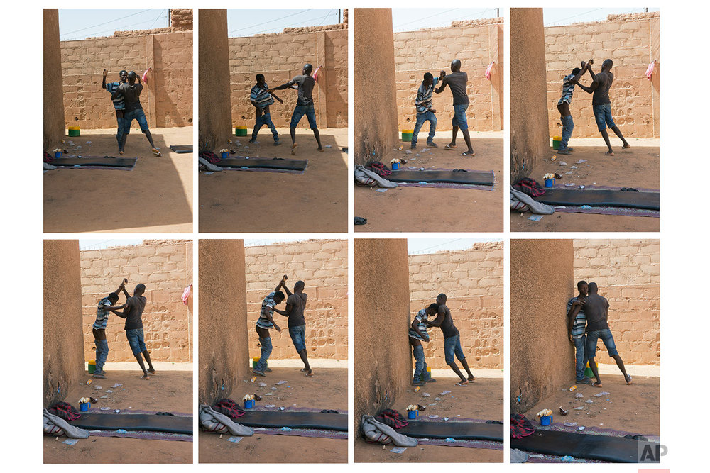A young migrant who has been expelled from Algeria is restrained by others after he attempted to strip naked in a transit center in Arlit, Niger, on June 2, 2018. (AP Photo/Jerome Delay)