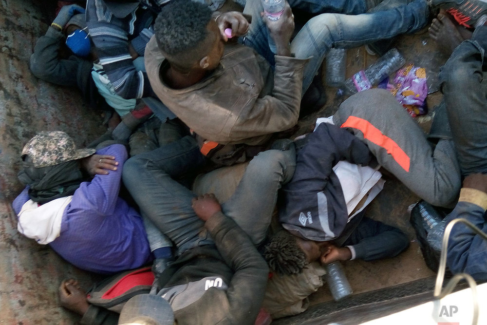 In this image taken Wednesday May 9, 2018 and provided by Ju Dennis, migrants being expelled from Algeria are trucked towards the Niger border. (AP Photo/Ju Dennis)