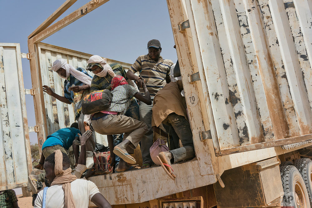 Migrants climb into a truck to head north into Algeria at the Assamaka border post in northern Niger on Sunday, June 3, 2018. (AP Photo/Jerome Delay)