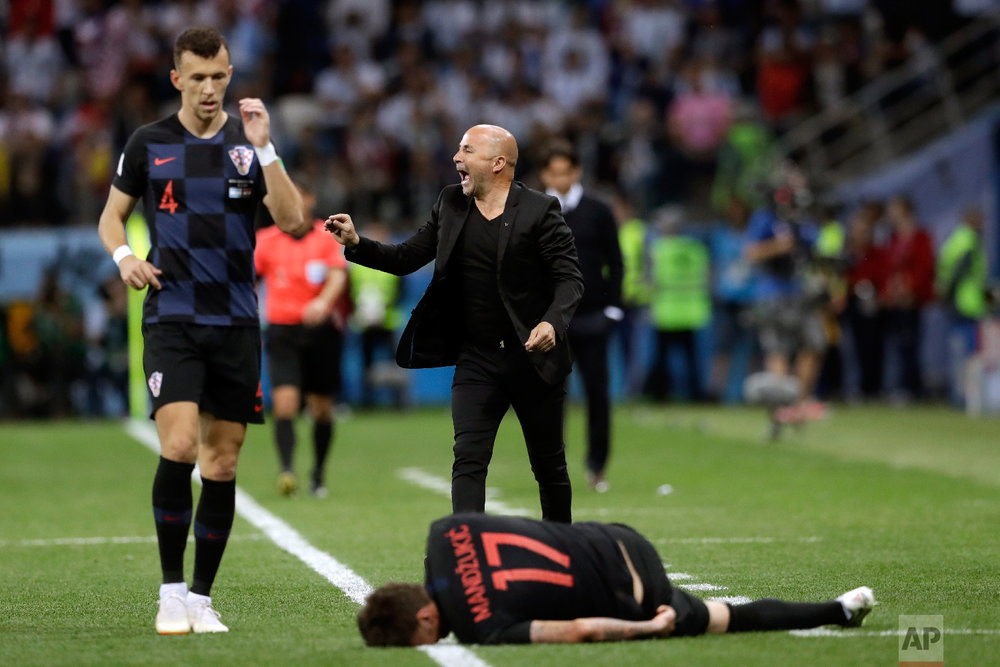 Argentina coach Jorge Sampaoli gives instructions to his players as Serbia's Ivan Perisic passes by and Mario Mandzukic lies on the pitch, during the group D match between Argentina and Croatia at the 2018 soccer World Cup in Nizhny Novgorod Stadium in Nizhny Novgorod, Russia, Thursday, June 21, 2018. (AP Photo/Petr David Josek)