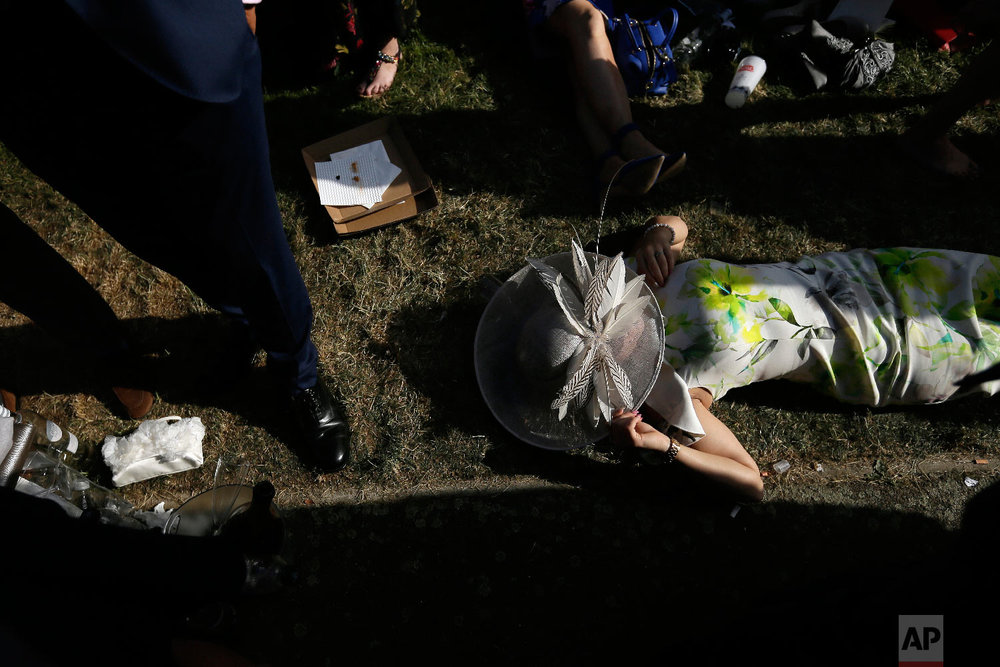 A racegoer rests between races on the third day of the Royal Ascot horse race meeting, which is traditionally known as Ladies Day, in Ascot, England Thursday, June 21, 2018. (AP Photo/Tim Ireland)
