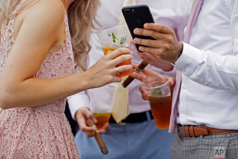 Racegoers enjoy drinks and cigars on the second day of the Royal Ascot horse race meeting in Ascot, England, Wednesday, June 20, 2018. (AP Photo/Tim Ireland)