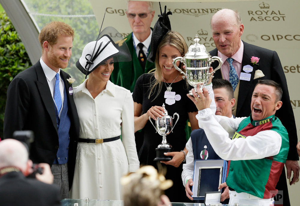 Britain's Prince Harry and Meghan, Duchess of Sussex present the trophy for the St James's Palace Stakes to Frankie Dettori, right, on the first day of the Royal Ascot horse race meeting in Ascot, England, Tuesday, June 19, 2018. (AP Photo/Tim Ireland)