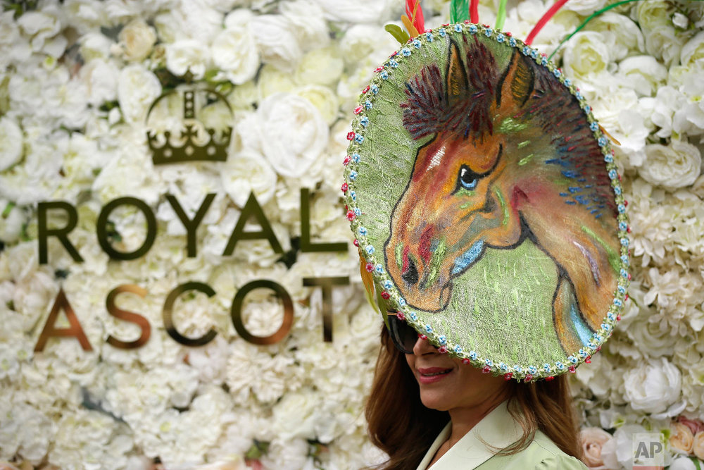 A racegoer poses for photographers on the first day of the Royal Ascot horse race meeting in Ascot, England, Tuesday, June 19, 2018. (AP Photo/Tim Ireland)