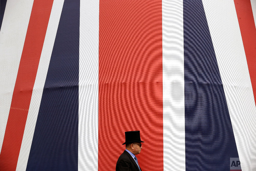 A racegoer walks past a huge British flag during the second day of the Royal Ascot horse race meeting in Ascot, England, Wednesday, June 20, 2018. (AP Photo/Tim Ireland)