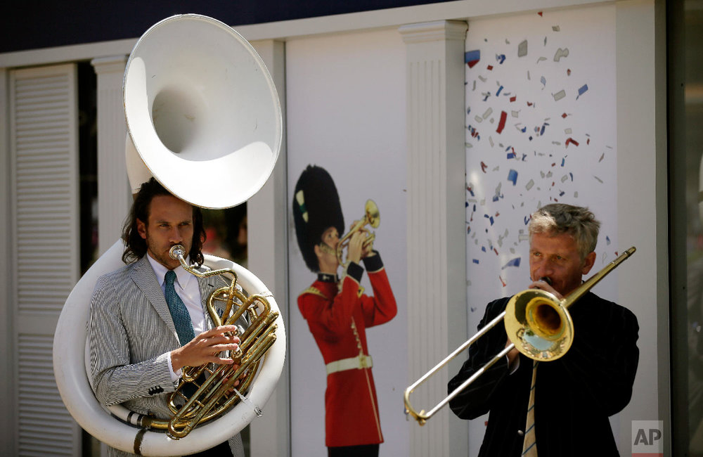 Musicians play instruments on the third day of the Royal Ascot horse race meeting, which is traditionally known as Ladies Day, in Ascot, England Thursday, June 21, 2018. (AP Photo/Tim Ireland)