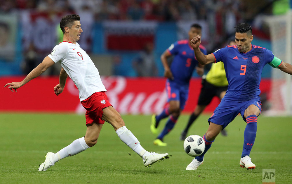 Poland's Robert Lewandowski, left, and Colombia's Radamel Falcao, right, challenge for the ball during the group H match between Poland and Colombia at the 2018 soccer World Cup at the Kazan Arena in Kazan, Russia, Sunday, June 24, 2018. (AP Photo/Thanassis Stavrakis)