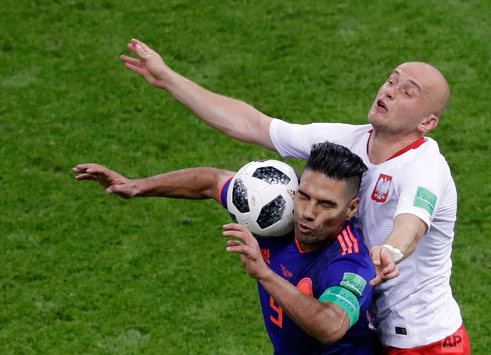 Colombia's Radamel Falcao, left, and Poland's Michal Pazdan battle for the ball during the group H match between Poland and Colombia at the 2018 soccer World Cup at the Kazan Arena in Kazan, Russia, Sunday, June 24, 2018. (AP Photo/Sergei Grits)