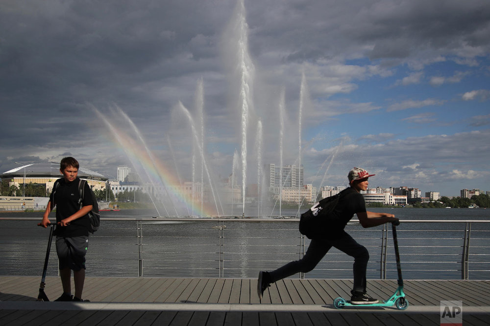 Children ride their scooters on the banks of Kazanka river during the 2018 soccer World Cup in Kazan, Russia on June 21, 2018. (AP Photo/Thanassis Stavrakis)