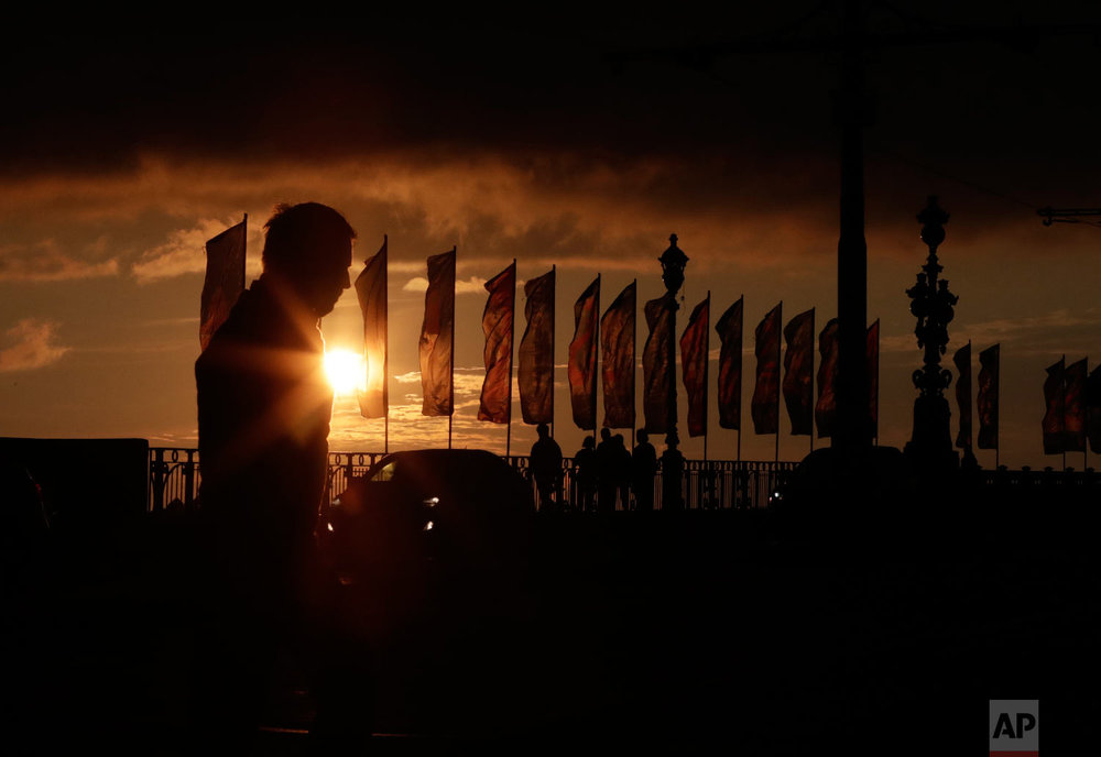 Visitors and banners for the 2018 soccer World Cup are silhouetted in St. Petersburg, Russia on June 24, 2018. (AP Photo/Lee Jin-man)