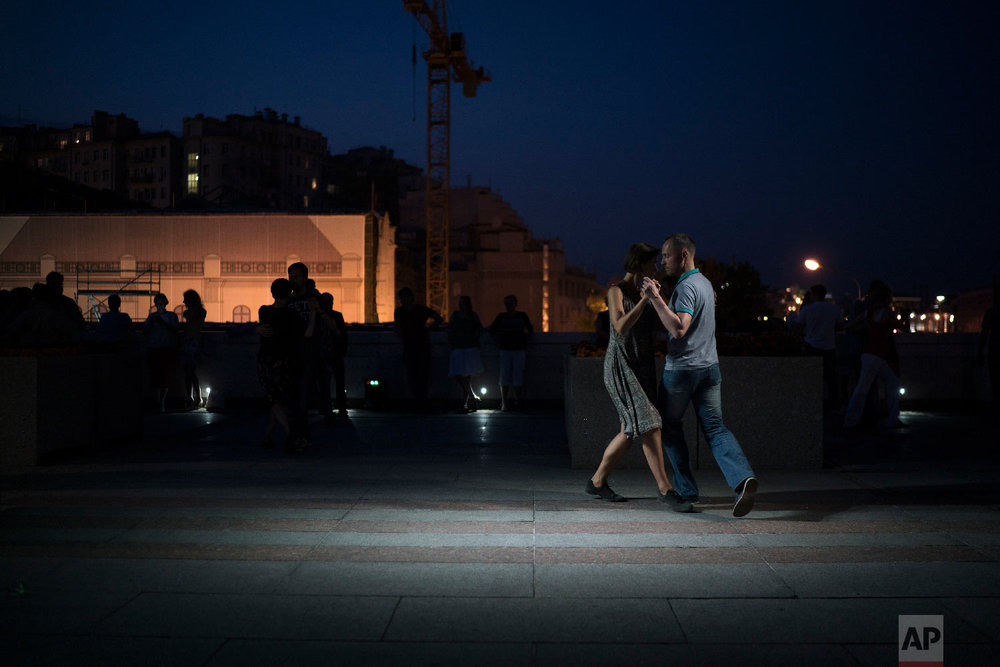 A couple dances tango on a bridge in central Moscow, during the 2018 soccer World Cup in Russia on June 22, 2018. (AP Photo/Felipe Dana)