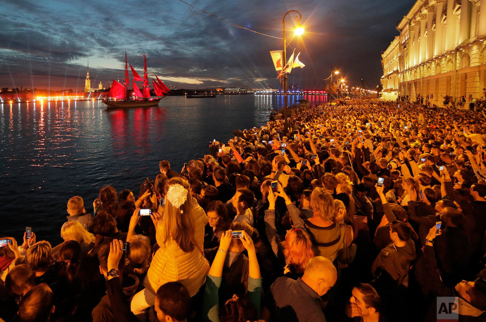 People watch a brig with scarlet sails on the Neva River during the Scarlet Sails festivities marking school graduation in St.Petersburg, Russia on June 24, 2018. (AP Photo/Dmitri Lovetsky)