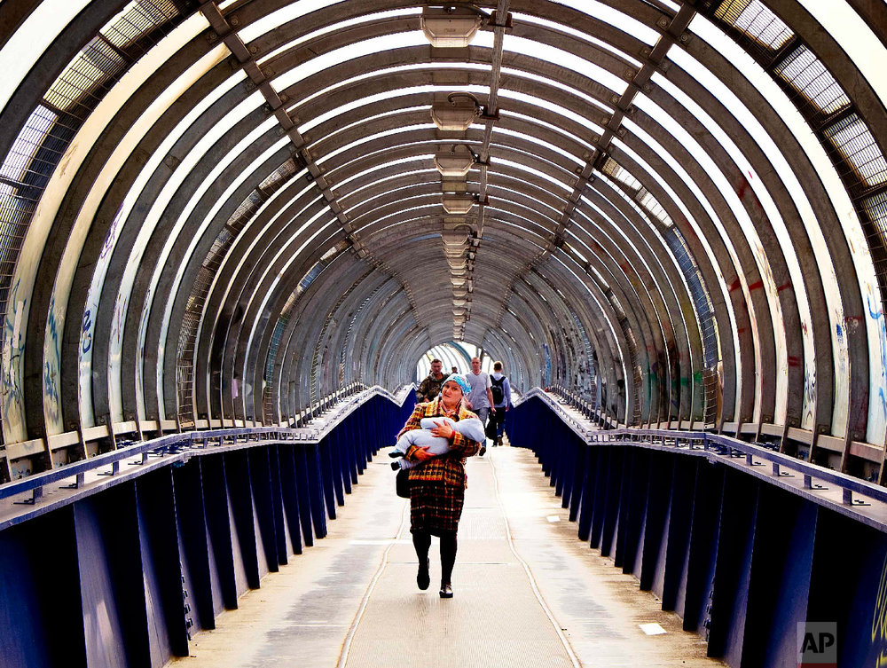 A woman carries a baby through a pedestrian bridge over a highway during the 2018 soccer World Cup in Podolsk near Moscow, Russia on June 19, 2018. (AP Photo/Michael Probst)