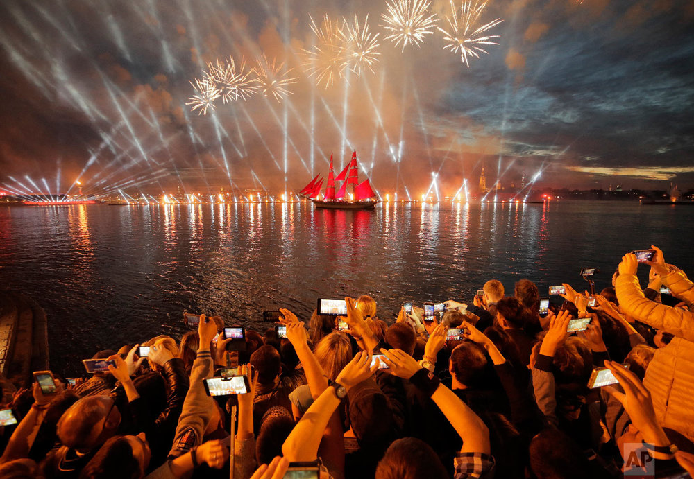 People watch fireworks and a brig with scarlet sails on the Neva River during the Scarlet Sails festivities marking school graduation in St.Petersburg, Russia on June 24, 2018. (AP Photo/Dmitri Lovetsky)