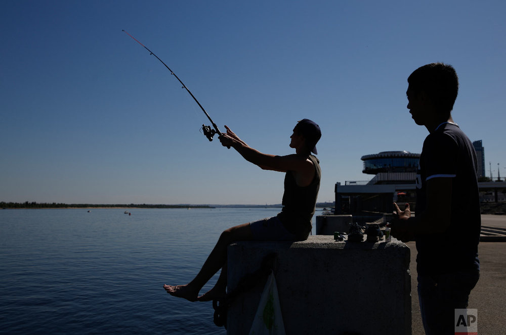 Young men fish along the banks of the Volga River during the 2018 soccer World Cup in Volgograd, Russia on June 18, 2018. (AP Photo/Rebecca Blackwell)