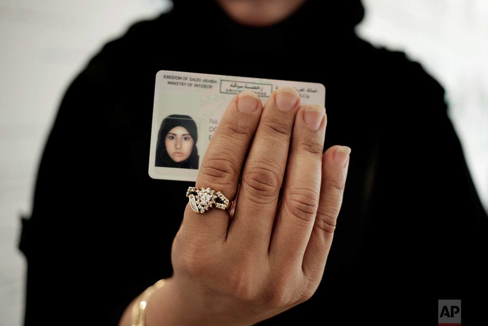 In this June 23, 2018 photo, a Saudi woman covering her name holds her new car license at the Saudi Driving School inside Princess Nora University in Saudi Arabia. As Saudi Arabia prepares to lift a ban on women driving, Saudi women are being pushed to the forefront of a major transformation being spearheaded by the country's Crown Prince Mohammed bin Salman. It also places women in the crosshairs of a decades-old pull-and-tug between Saudis agitating for more social openings and a majority that remains deeply conservative. (AP Photo/Nariman El-Mofty)