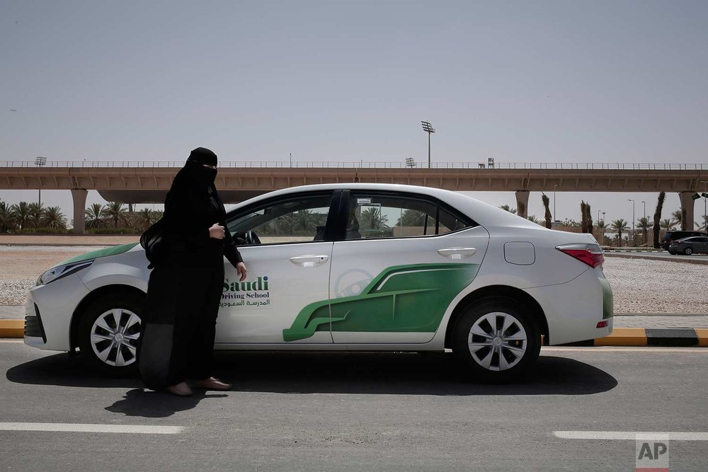 In this June 23, 2018 photo, 27-year old driving instructor Mabkhoutah al-Mari stands next to a test drivers car at the Saudi Driving School inside Princess Nora University in Saudi Arabia. (AP Photo/Nariman El-Mofty)