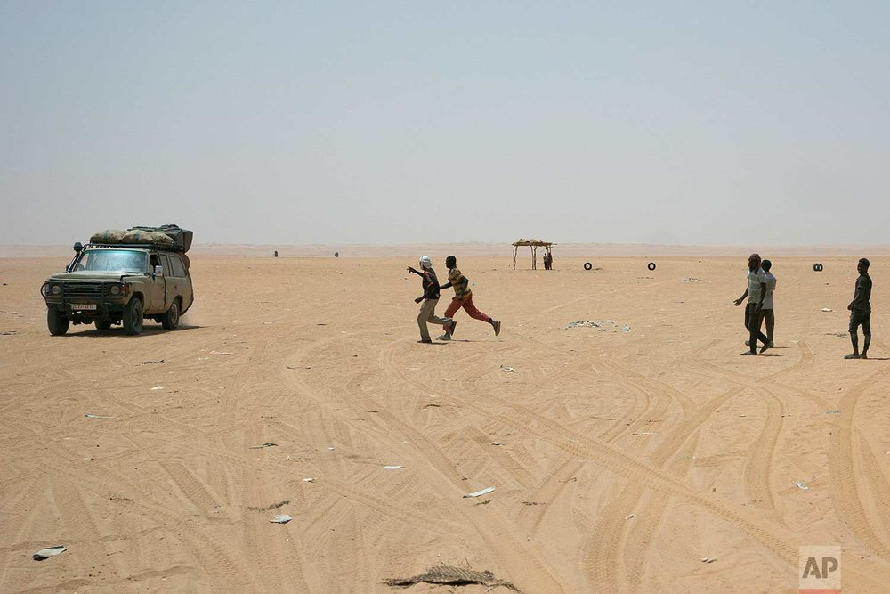 "Migrants and locals wait for trucks arriving from Algeria to unload their cargo on Sunday, June 3, 2018, in order to earn money to pay for the trip north, at a giant desert trading post called ""The Dune"" in the no-man's land separating Niger and Algeria north of the Assamaka border post in northern Niger. (AP Photo/Jerome Delay)"