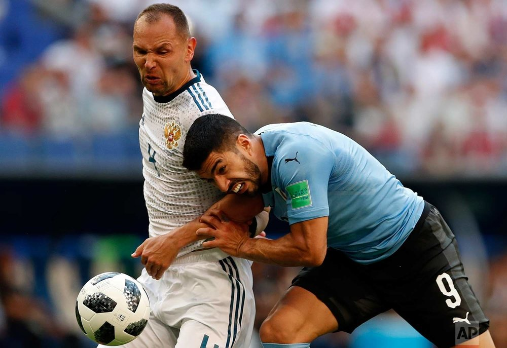 Uruguay's Luis Suarez, right, and Russia's Sergei Ignashevich fight for the ball during the group A match between Uruguay and Russia at the 2018 soccer World Cup at the Samara Arena in Samara, Russia, Monday, June 25, 2018. (AP Photo/Rebecca Blackwell)