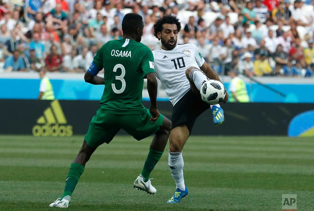 Saudi Arabia's Osama Hawsawi, left, and Egypt's Mohamed Salah challenge for the ball during the group A match between Saudi Arabia and Egypt at the 2018 soccer World Cup at the Volgograd Arena in Volgograd, Russia, Monday, June 25, 2018. (AP Photo/Darko Vojinovic)