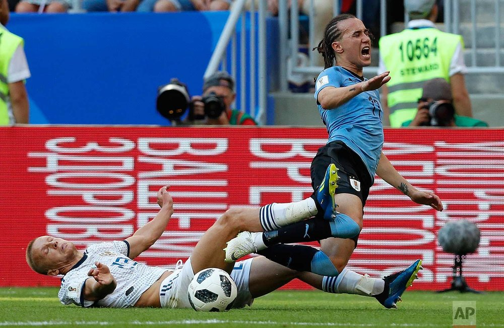 Russia's Igor Smolnikov, left, and Uruguay's Diego Laxalt challenge for the ball during the group A match between Uruguay and Russia at the 2018 soccer World Cup at the Samara Arena in Samara, Russia, Monday, June 25, 2018. (AP Photo/Hassan Ammar)