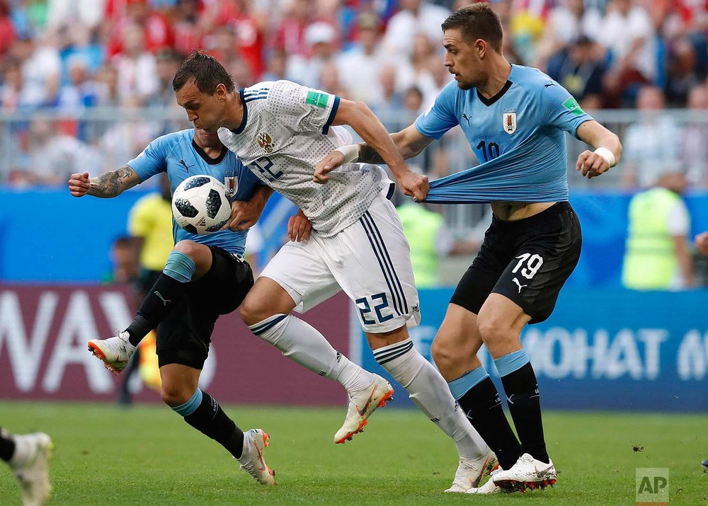 Uruguay's Lucas Torreira, from left, Russia's Artyom Dzyuba and Uruguay's Sebastian Coates challenge for the ball during the group A match between Uruguay and Russia at the 2018 soccer World Cup at the Samara Arena in Samara, Russia, Monday, June 25, 2018. (AP Photo/Hassan Ammar)