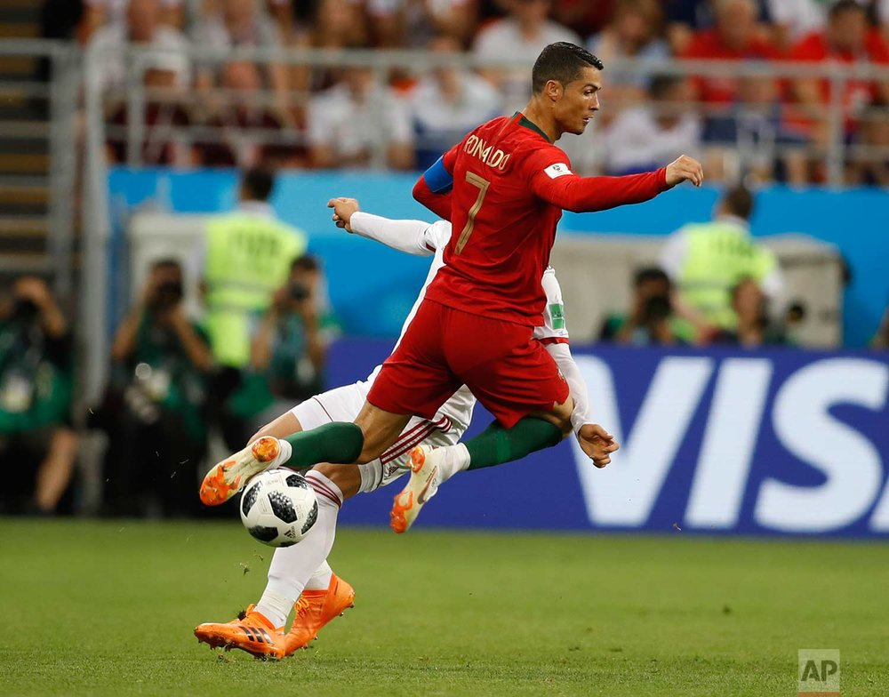 Portugal's Cristiano Ronaldo, collides with Iran's Alireza Jahanbakhsh during the group B match between Iran and Portugal at the 2018 soccer World Cup at the Mordovia Arena in Saransk, Russia, Monday, June 25, 2018. (AP Photo/Francisco Seco)