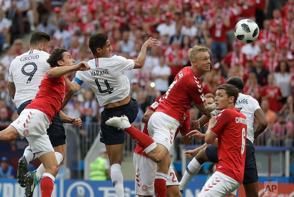 Denmark's Simon Kjaer, top centre right, heads the ball under pressure from France's Raphael Varane top center left, during the group C match between Denmark and France at the 2018 soccer World Cup at the Luzhniki Stadium in Moscow, Russia, Tuesday, June 26, 2018. (AP Photo/Matthias Schrader)